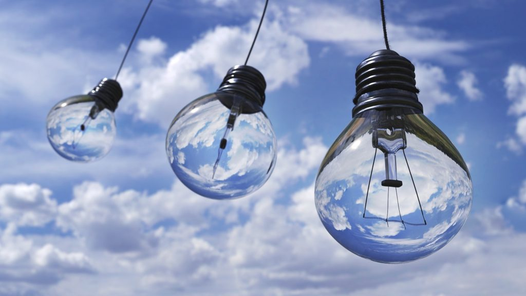 Light bulbs against blue sky filled with clouds to represent utility companies