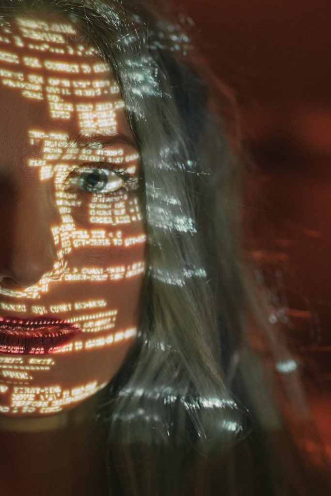 girl with code projecting on her face representing the risk of ransomware attacks